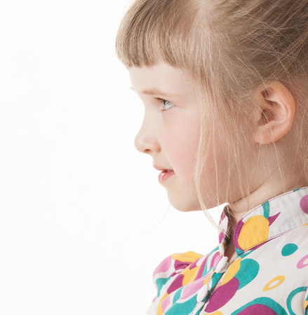sideview: Portrait of a pretty little girl on white background, sideview Stock Photo