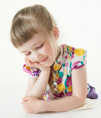 upgrowth: Pretty little girl lying on the floor and looking on her drawing, white background Stock Photo