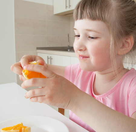 upgrowth: Happy little girl eating a tasty orange at home