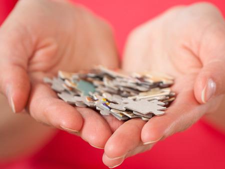 Female hands holding many puzzles - closeup shot Banco de Imagens