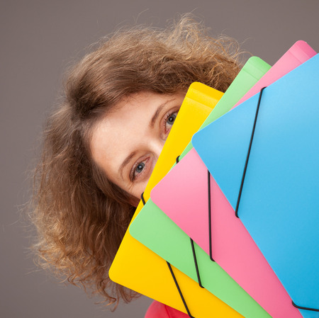 upgrowth: Young woman holding bright folders, gray background Stock Photo