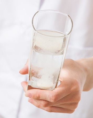 fizzy tablet: Doctor holding a glass with drug , white background