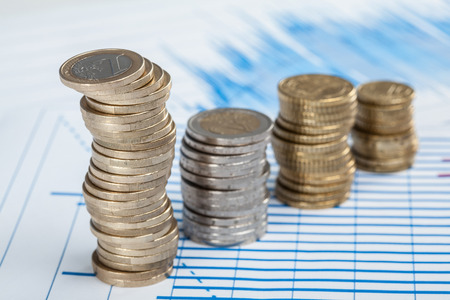 monetary devaluation: Four columns of coins on the table, closeup shot