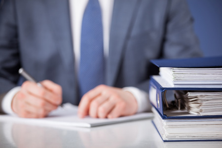 Businessman signing documents, blue background Stock Photo