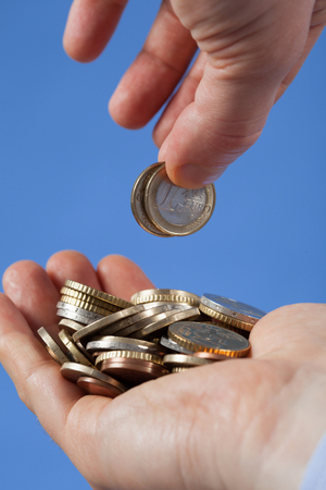 Male hand puts coins in the palm his partner, blue background