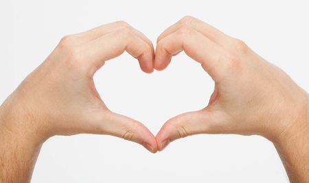 forming: Hands forming a heart on white background
