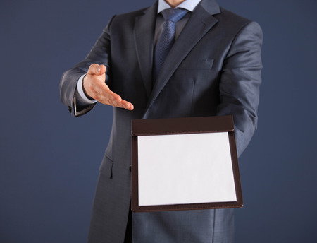 proposing: Businessman holding a clipboard with empty sheet of paper, dark  background