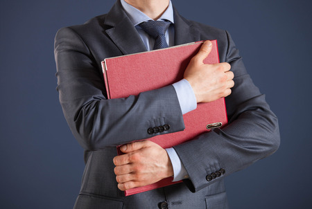 folder with documents: Unrecognizable businessman holding folder with documents. dark background