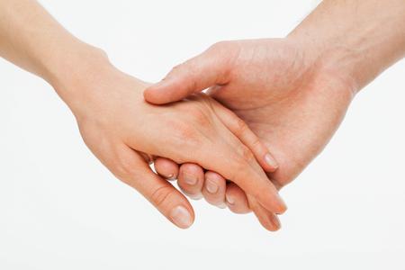 manos entrelazadas: la mano del hombre que sostiene suavemente la mano de la mujer - tiro del primer