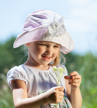 wild flowers: Smiling little girl holding wild flowers outdoors Stock Photo