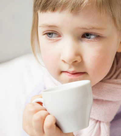 convalesce: Portrait of a little girl sitting in a bed with cup