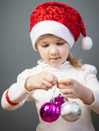 charming girl: Portrait of a charming little girl in Santas hat, grey background