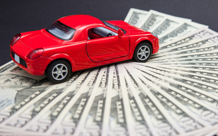 lading: Toy red car on dollars, dark background Stock Photo