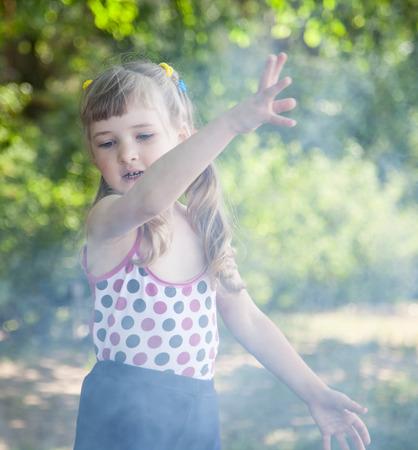 disperse: Little girl dispersing smoke in a summer park