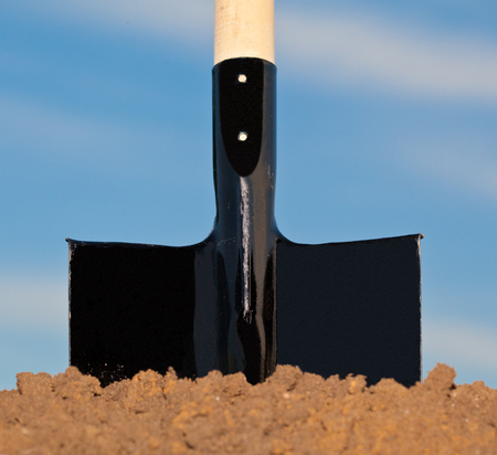 bury: Shovel in the heap of ground against blue sky Stock Photo