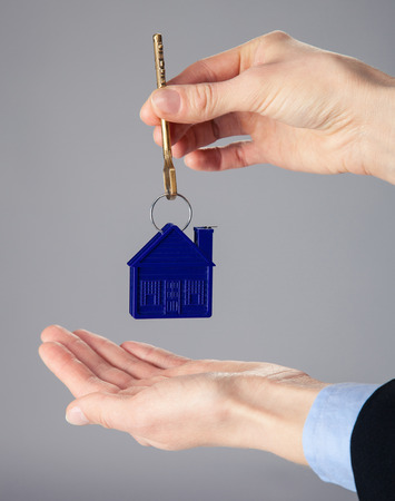 reach customers: Real estate agents hands holding a key from a house, closeup shot Stock Photo