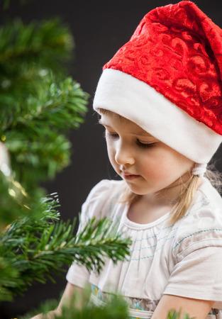 decorates: Beautiful little girl decorates the Christmas tree, dark background Stock Photo