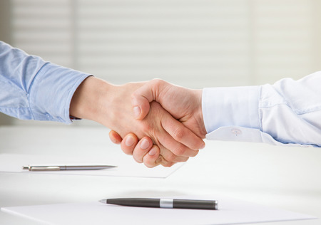 paper work: Successful business people shaking hands while making agreement Stock Photo