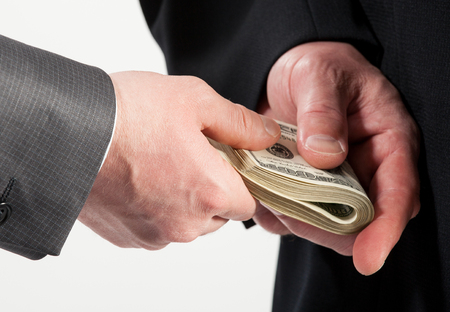 venality: Businessman giving a bribe, neutral background Stock Photo