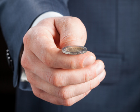 Businessman tossing a coin Stock Photo