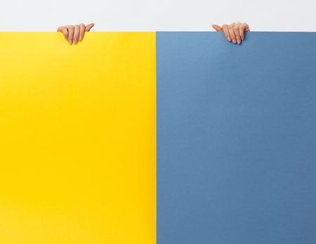 yellow paper: Hands holding yellow and blue paper boards, white background Stock Photo