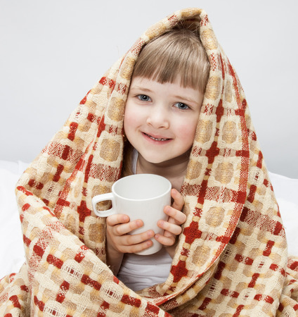 convalescence: Portrait of a little girl covering with a rug and holding a white cup