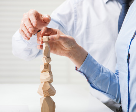 mujeres juntas: La gente de negocios que construyen la torre de madera (juego japonés tumi-ishi), que ilustran el concepto de éxito del negocio, la cooperación, el logro y el autocontrol Foto de archivo