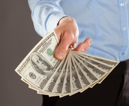 reaching out: Womans hand reaching out money on grey background Stock Photo