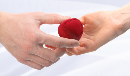 expanding: Mans hand expanding red velvet heart-shaped box to womans hand, neutral background