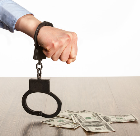 young  cuffs: Hands in handcuffs and money  on the table; white background Stock Photo