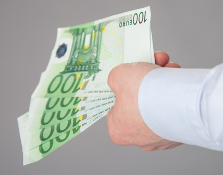 reaching out: Businessmans hand reaching out euro banknotes