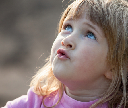Adorable little girl looking up - closeup portrait Stock Photo