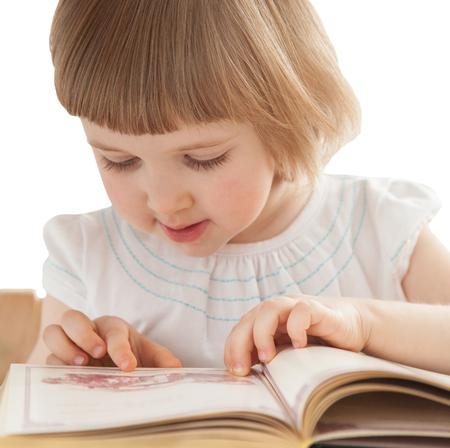 jolie petite fille: Jolie petite fille lisant un livre intéressant; isolé sur blanc Banque d'images