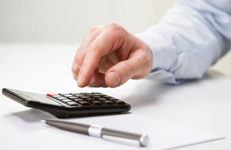 calculadora: La mano del empresario irreconocible que usa la calculadora - tiro del primer