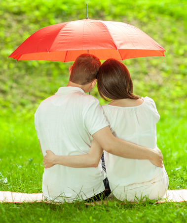 love in rain: Couple in love sitting on green summer meadow under red umbrella embracing each other