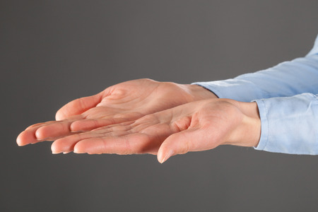 outstretched: Womans hands outstretched, grey background Stock Photo