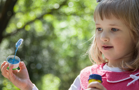 charming girl: Charming little girl making soap bubbles in a summer park Stock Photo