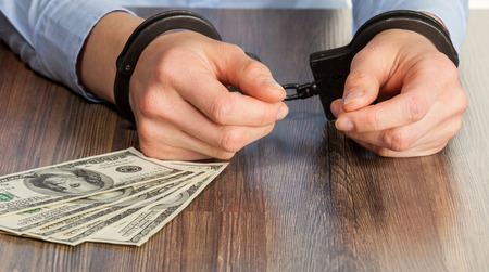 entrap: Hands in handcuffs on the table
