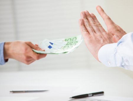 refusing: Businessman refusing to take a bribe, closeup shot of hands over the table