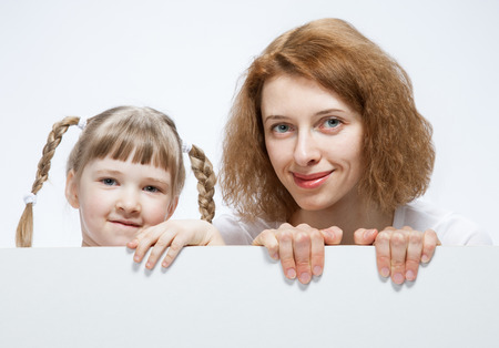 neutral background: Happy young mother with her smiling daughter, neutral background