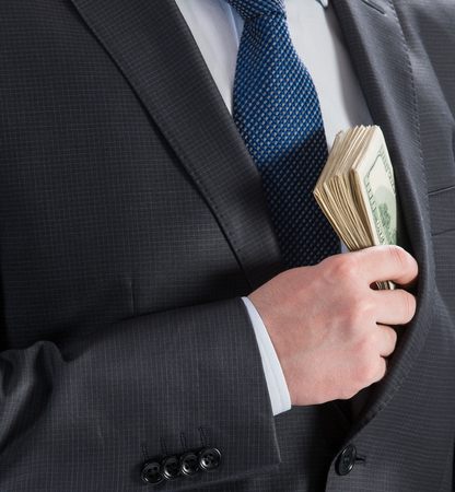 corruptible: Businessman putting money in his pocket - closeup shot