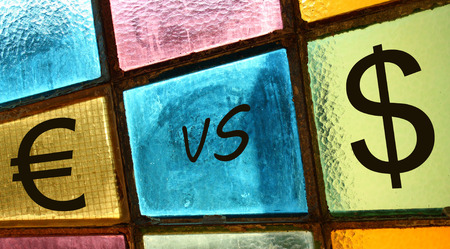 versus: Euro versus dollar; euro and dollar signs painted on a stained-glass window Stock Photo