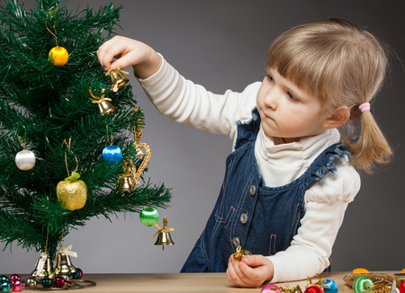sincere girl: Beautiful little girl decorates the Christmas tree, dark background Stock Photo