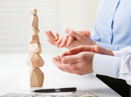 goal achievement: Business people applauding near built wooden tower (Japanese game tumi-ishi), illustrating concept of business success, cooperation, achievement and self-control Stock Photo