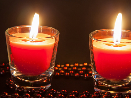 festal: Two small burning candleson dark background