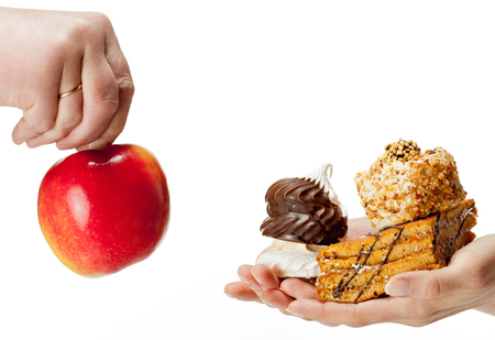 dietology: Hands proposing apple (healthy food) and cakes (unhealthy food) to each other. Concept of making a choice: healthy low-calorie or unhealthy high-calorie food?  Isolated on white