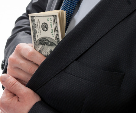 venal: A businessman in a black suit putting money in his pocket isolated on white background