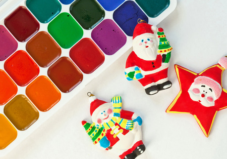 neutral background: Colorful paints set and new year toys painted by a child; neutral background