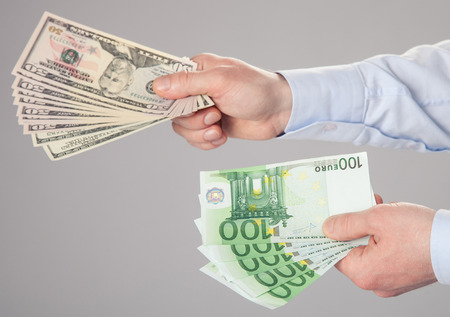 hands reaching: Businessmans hands reaching out dollar and euro banknotes