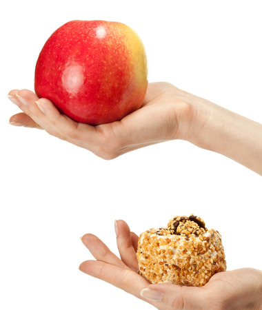 dietology: Healthy or unhealthy food? Hand holding apple and cake demonstrating process of choosing